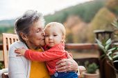 Elderly Woman Kissing A Toddler Great-grandchild On A Terrace In Autumn. poster