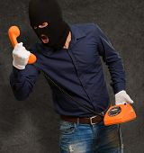 Burglar Man Holding Telephone On Wall