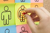 stock photo of niche  - Hand pinning a sticky note in the center of a customer target on cork board - JPG