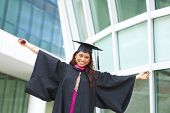 Excited Indian female graduate open arms