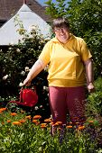 Disabled Woman With A  Pot Pours Flowers
