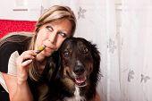 Постер, плакат: Молодой блондинке с собака смешанной породы испарялась E сигареты