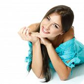 Beautiful teen girl lying in blue dress  and smiling. Isolated on white background