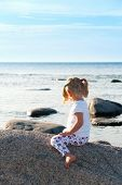 stock photo of straddling  - Rear view of a little girl straddling a boulder on the beach as she sits in the summer sunshine looking out to sea - JPG