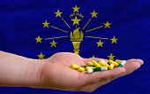 Holding Pills In Hand In Front Of Indiana Us State Flag
