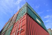 Upward view for stack of Cargo Containers under blue sky at sunrise in an intermodal yard.