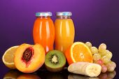 Delicious multifruit juice in a bottle and fruit next to it on purple background