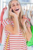 Blonde Frau in einem Bekleidungsgeschäft lachen, während sie am Telefon ist