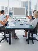 Business people applauding during a video conference while they are sat in the boardroom