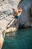 Deep water soloing, female climber on cliff