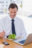 Smiling businessman eating a salad on his desk during the lunch time