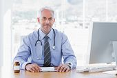 Attractive doctor sitting at his desk and looking at camera