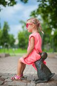 Cute Girl Astride On A Duck Figure Of Iron And Having Fun