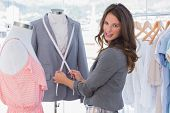 Attractive fashion designer measuring blazer and looking at the camera