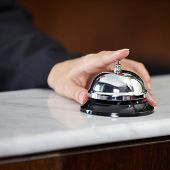 Female hand ringing hotel bell at the counter with index finger
