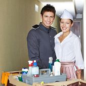 Friendliy service staff in hotel with bellboy and hotel maid