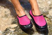Sapatos de água / nadar sapato em neoprene rosa em rochas na água na praia. Closeup detalhe dos pés de um