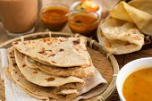Indian food, Chapati flatbread, roti canai, dal, curry, teh tarik or pulled tea, acar. Famous indian cuisine.