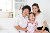 Family generations. Happy Asian family at home, grandparent, parent and grandchild sitting on sofa s