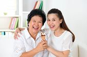 Sharing an ice cream. Happy Asian family sharing food at home. Beautiful senior mother and adult daughter eating dessert together.