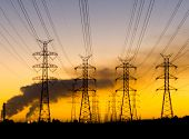 stock photo of transmission lines  - power transmission towers at dawn with power stations emitting smoke - JPG