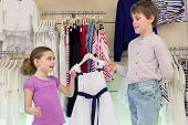 The brother helps sister to choose clothes in shop of children clothing