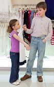 The boy helps girl to choose clothes in shop of childrens clothing