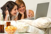 Teenagers friends enjoy movie night watching laptop and laughing