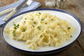 Fettuccine Alfredo with thyme on a rustic table