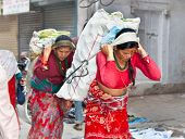 KATHMANDU, NEPAL - MAY 19: Nepalese women carry things in the traditional way on May 19, 2013 in Kat
