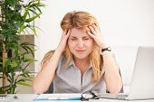 Mature woman with headache sitting at the table in the office