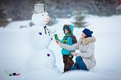 Little boy with his mother painting a snowman