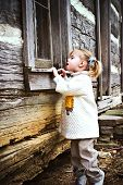 foto of log cabin  - Curious toddler looking inside an old log cabin - JPG