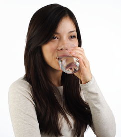 stock photo of drinking water  - Beautiful young woman drinking water on white background - JPG