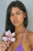 Brunette woman with pink orchid flower