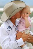 stock photo of baby cowboy  - Cowboy kissing his baby daughter with her making a face - JPG