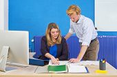 Two product engineers discussing technical drawings on a desk in an office