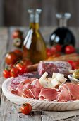 stock photo of smoked ham  - Italian antipasto with ham olive tomato cheese bread and salami selective focus - JPG