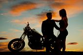 stock photo of seduce  - A silhouette of a man sitting on his bike holding on to his woman - JPG