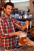 picture of bartender  - Portrait of young bartender tapping beer in pub - JPG