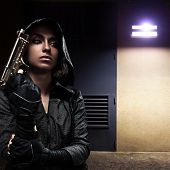 Danger woman with gun on night street.