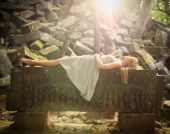 stock photo of cinderella  - Sleeping Beauty fairytale princess lying down on a stone altar in the forest - JPG