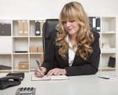 Blond businesswoman writing notes at her desk