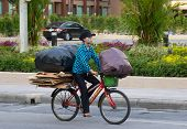 Patong  - April 26: Thai Woman Takes Out The Garbage In Bags On The Bike