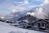 SWISS ALPS, SWITZERLAND - JAN 05 2014 : Dog walkers stroll down towards the village of Falera, Gaubu