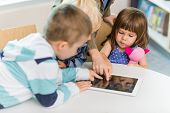 Cute girl with friends using digital tablet at table in school library
