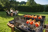 stock photo of meats  - Shashlick laying on the grill with a group of friends in the background eating and drinking in the late sunny afternoon - JPG