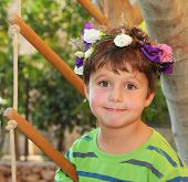 Cheerful birthday beautiful boy in the park. The boy wore a wreath of flowers