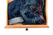 High angle shot of a pair of blue jeans crumpled up in a dresser drawer. Horizontal format isolated