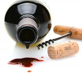 Closeup of a red wine bottle with a drip and wine spill in the foreground. A cork screw and cork to